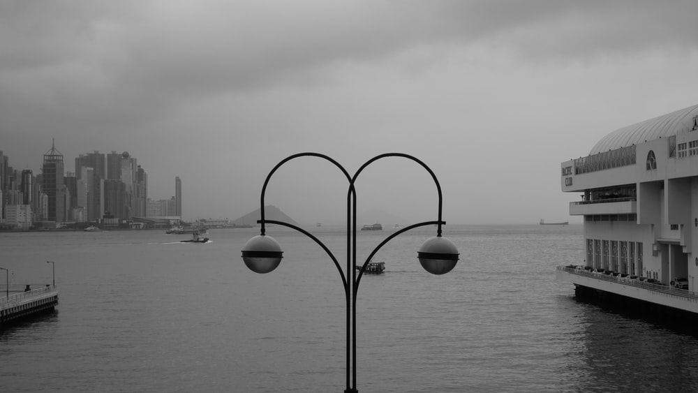 grayscale photography of buildings and body of water