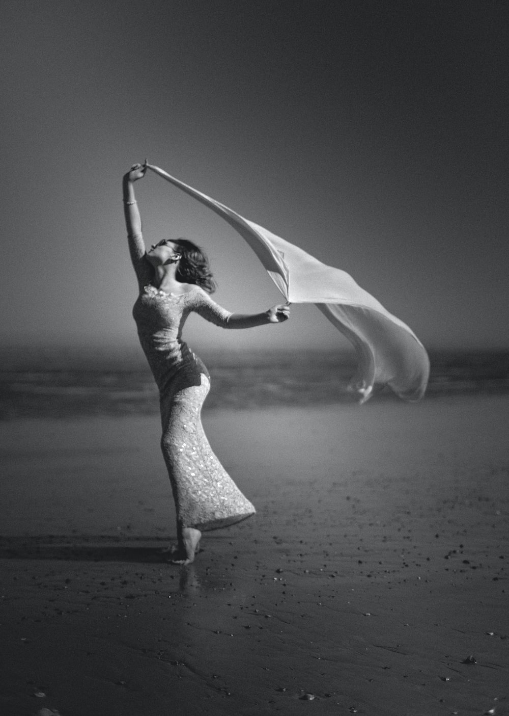 grayscale photography of woman standing on shore while holding scarf