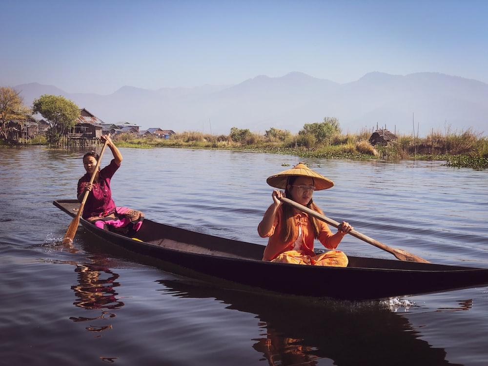 two women rowing boat wearing conical hats