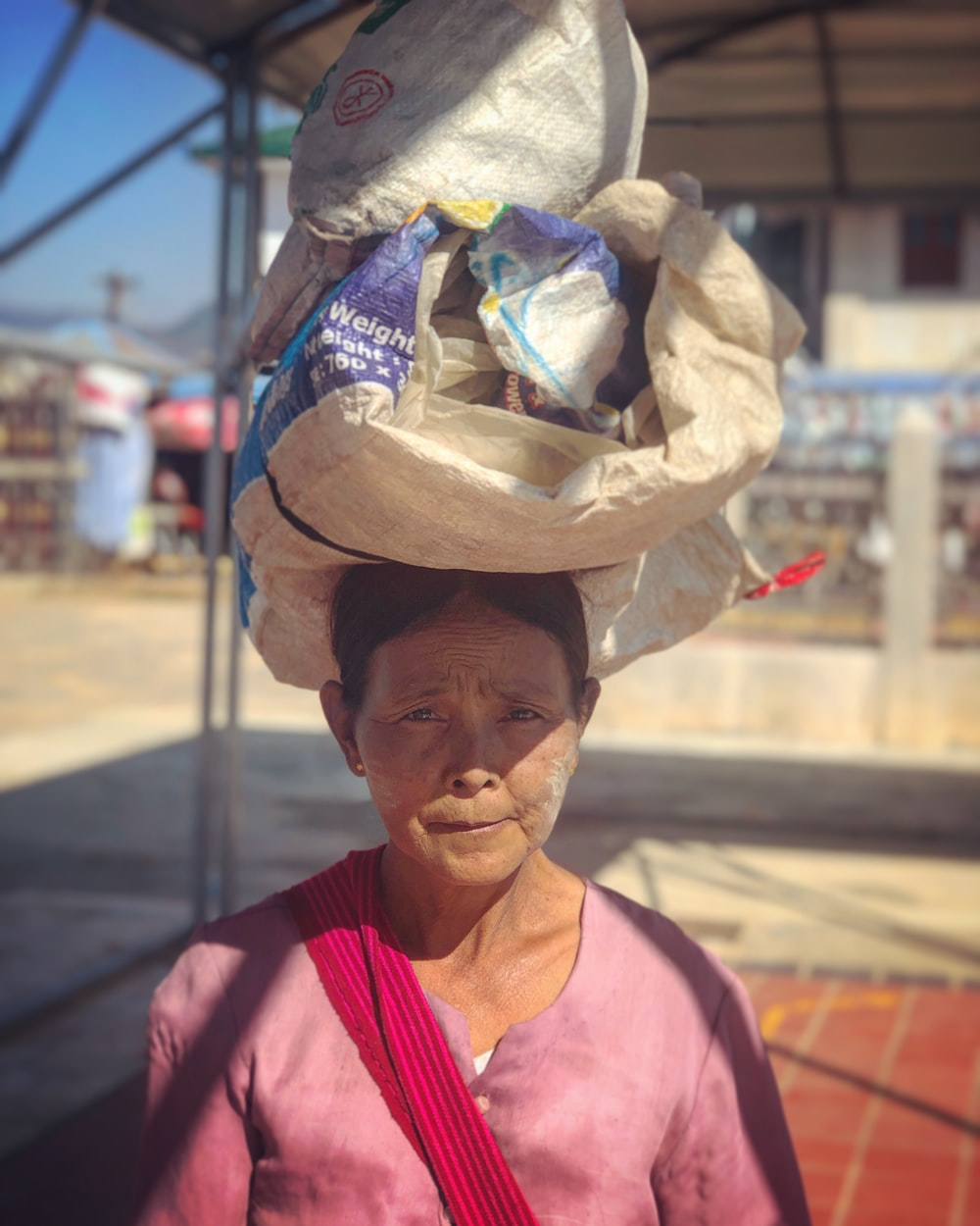 woman carrying sack on her head during daytime