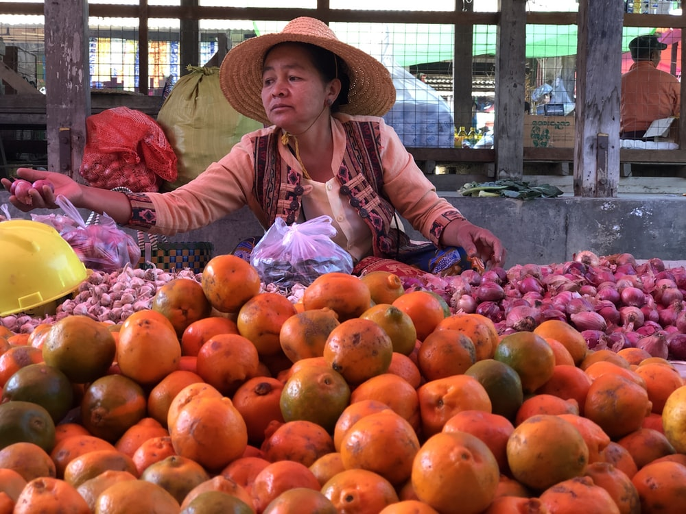 woman wearing straw hat selling fruits and vegetables during daytime