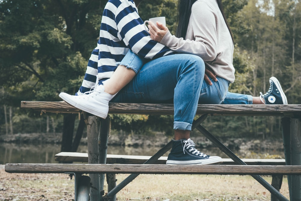 man and woman sitting on brown wooden bench