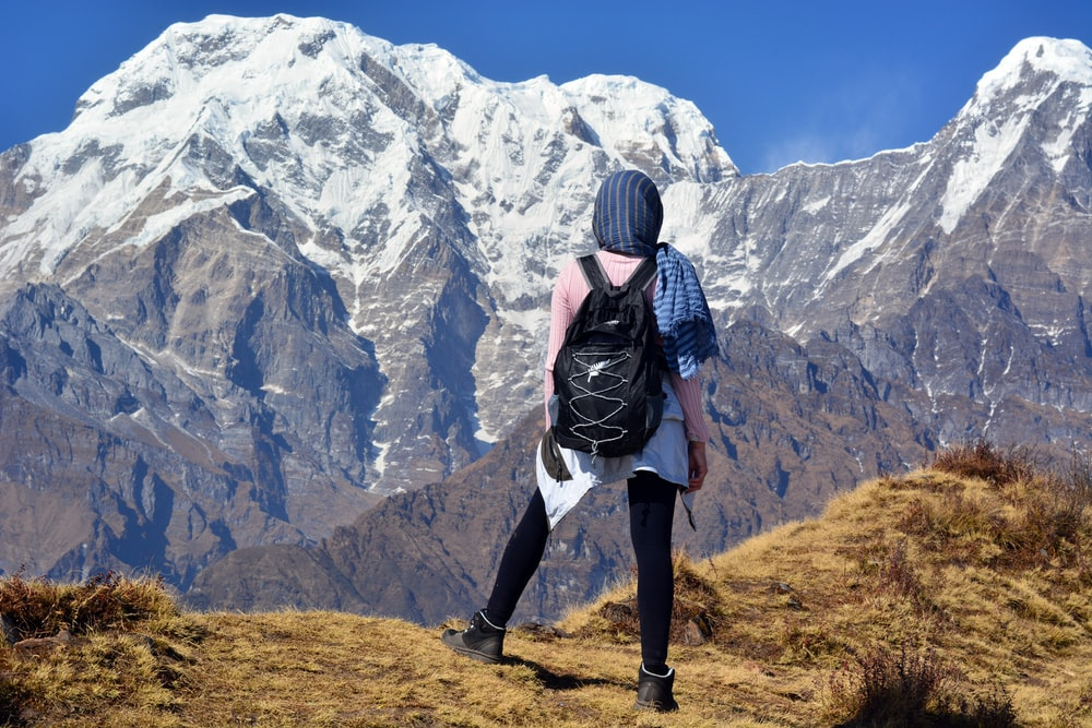 person carrying black backpack across white mountain