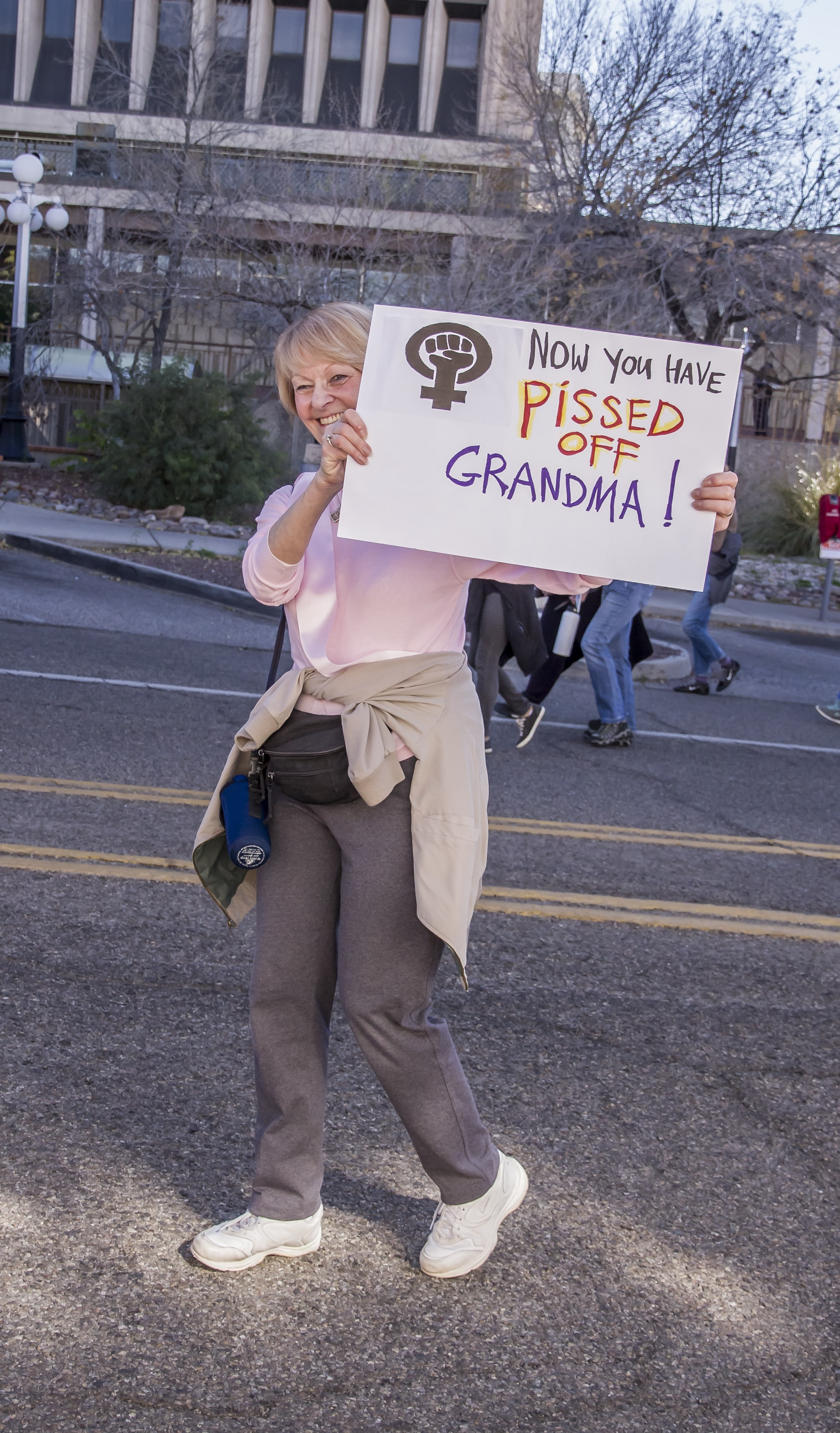woman walking while holding now you have pissed off grandma! sign