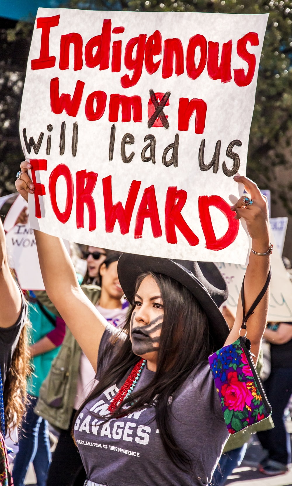 woman raising white and red sign with indigenous women will lead us forward text