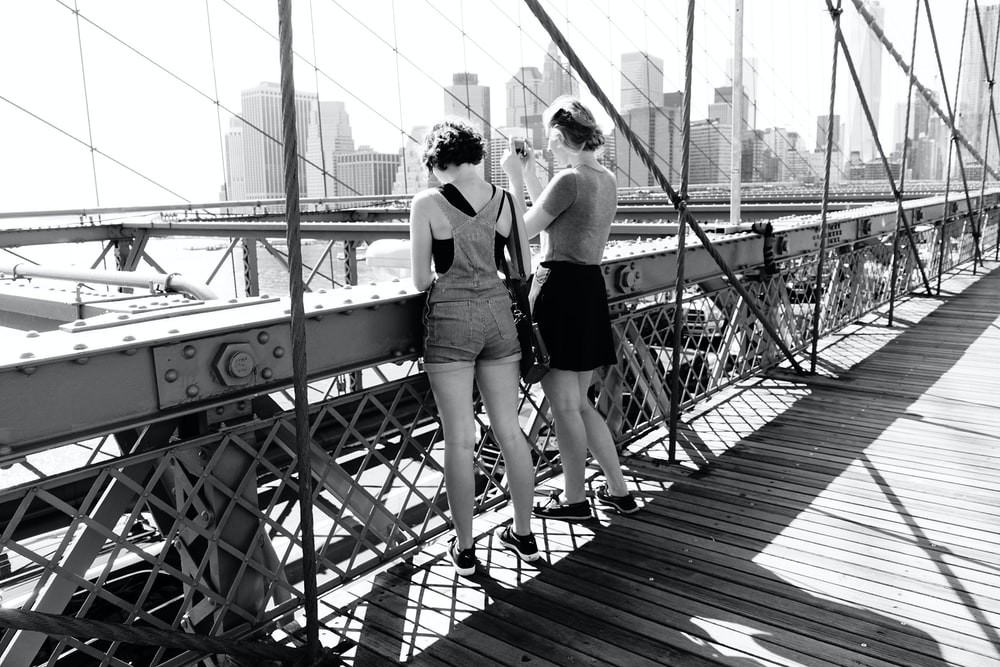 two women standing on bridge