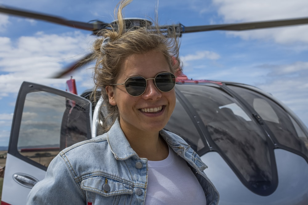 woman smiling in front of helicopter