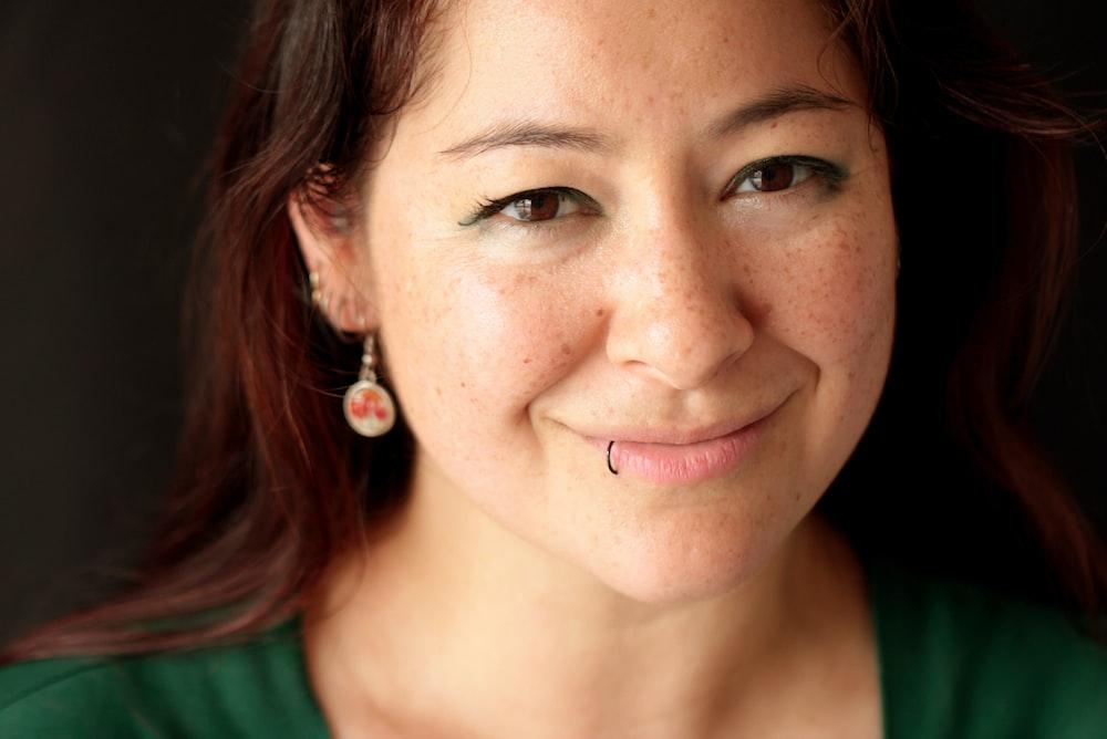 緑のトップを着て笑顔の女性