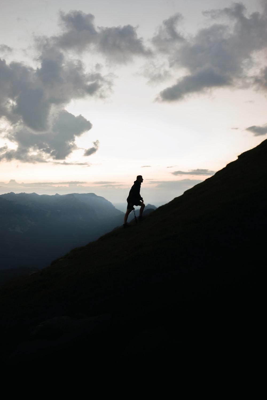 man climbing up the peak under grey cloudy sunset sky