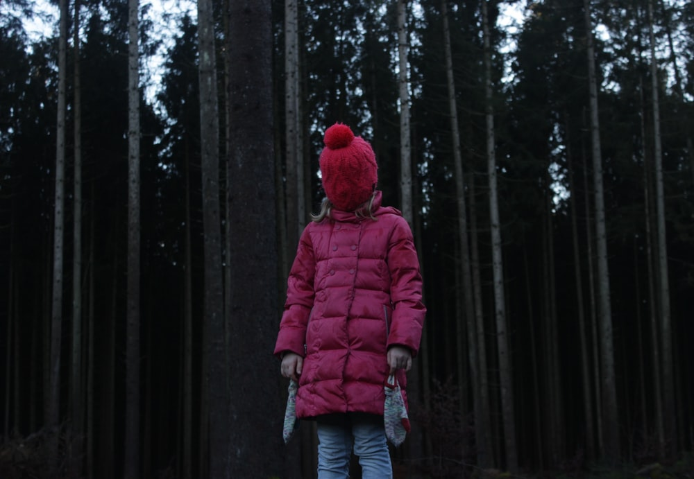 person in pink coat standing near trees
