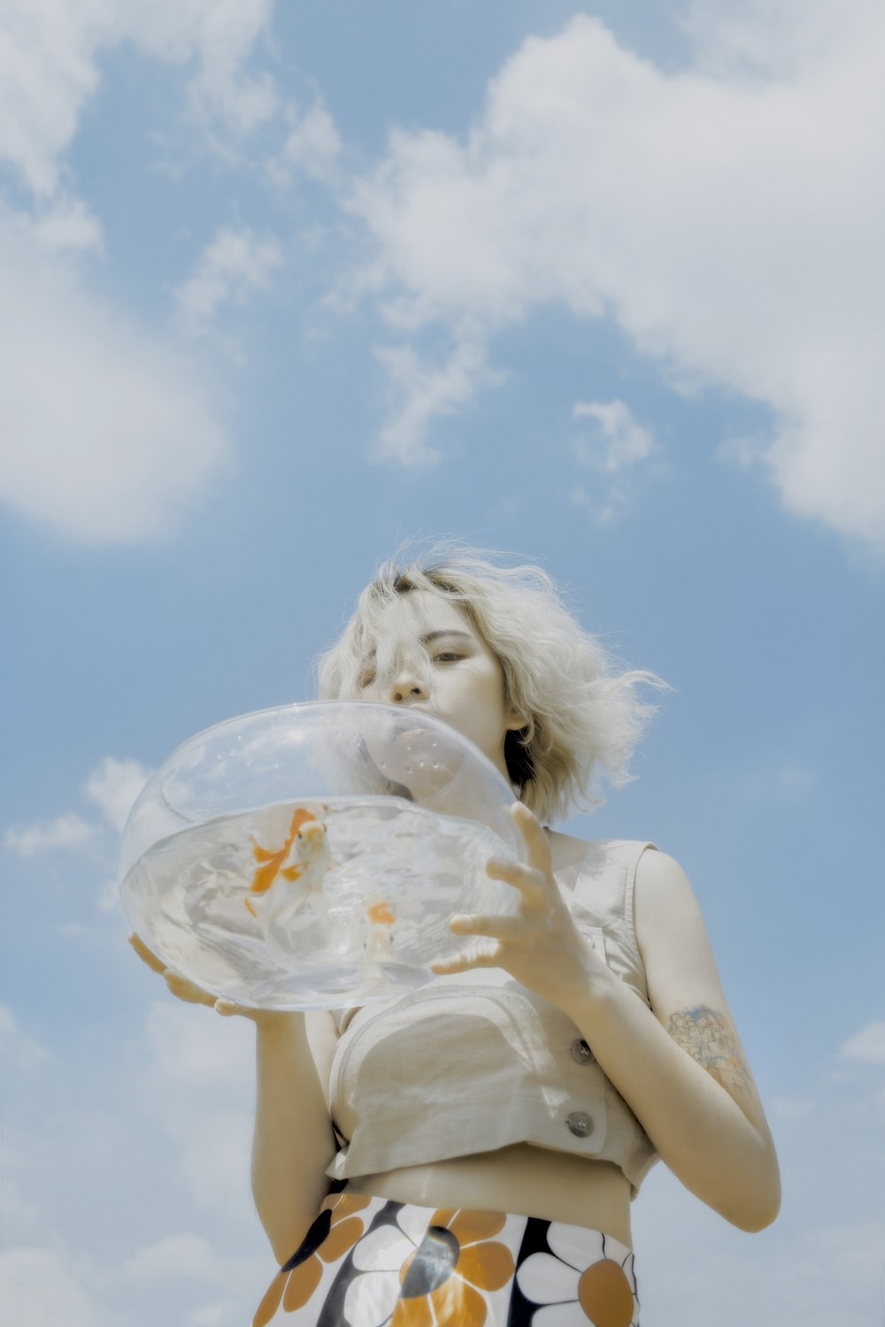 woman holding round clear glass fishbowl with live fish under white and blue sky