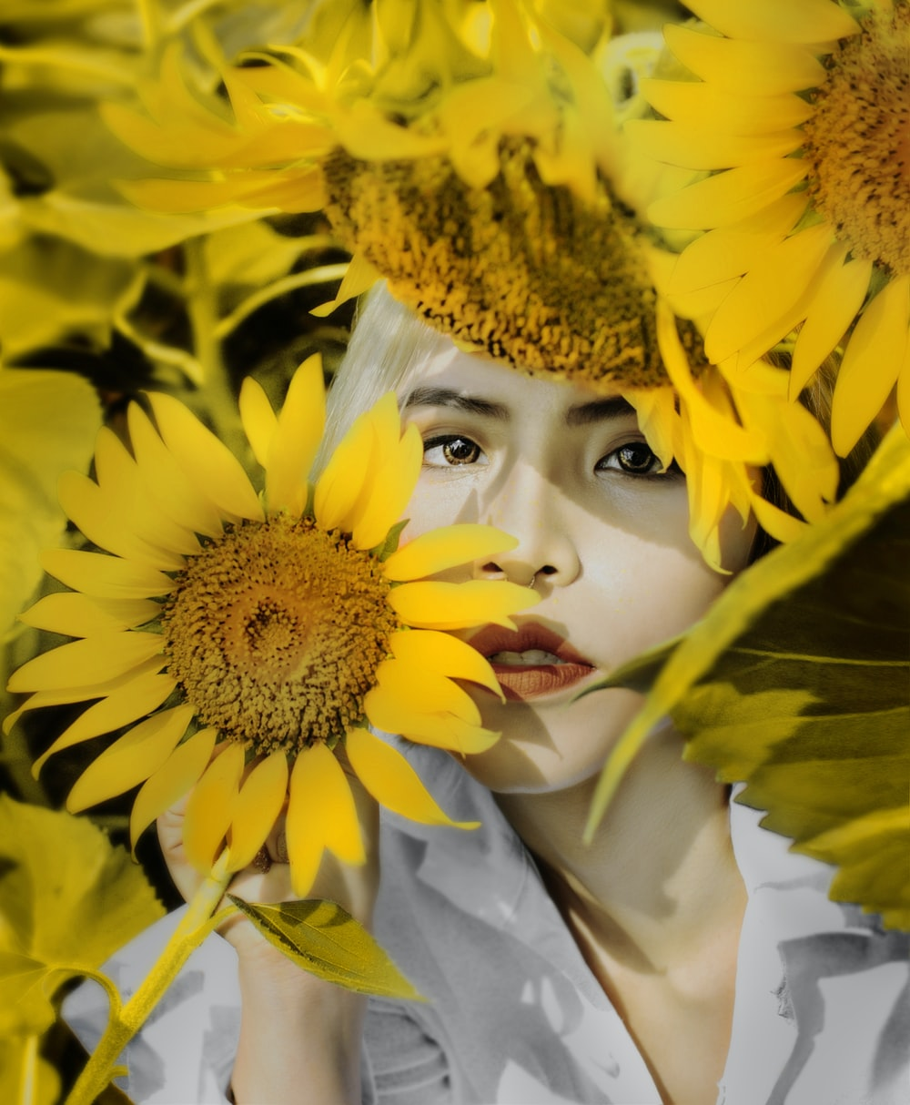 woman under shade and holding sunflower in selective focus photography