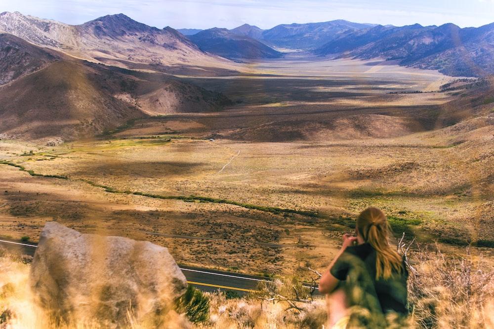woman sitting near mountains