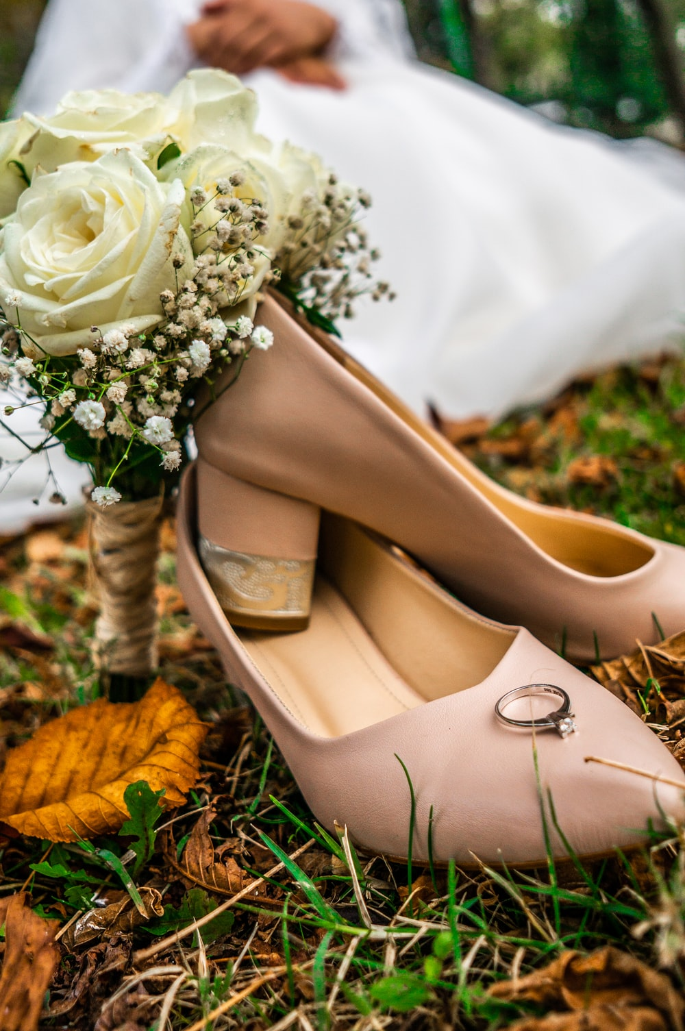 gold solitaire ring placed on top brown leather shoe on grass