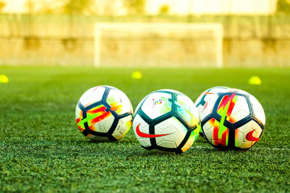 three white-and-black soccer balls on field
