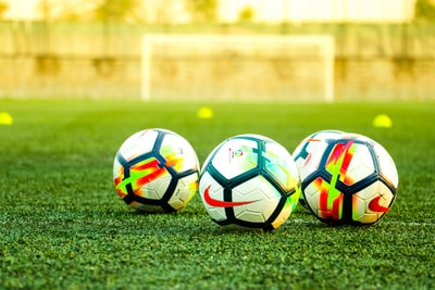 three white-and-black soccer balls on field soccer teams background