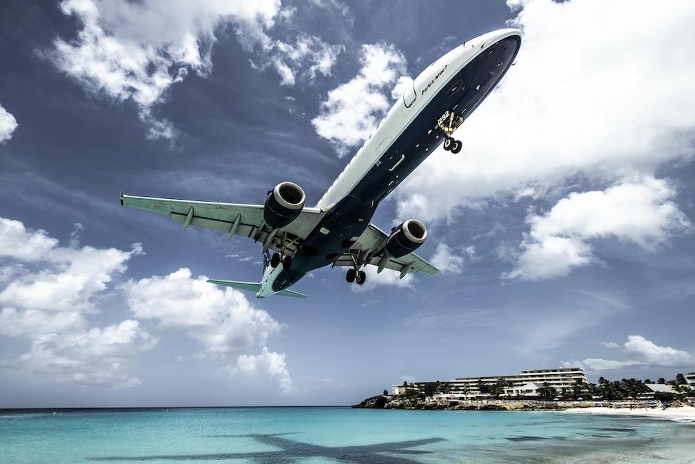 white aircraft above beach shoreline at daytime