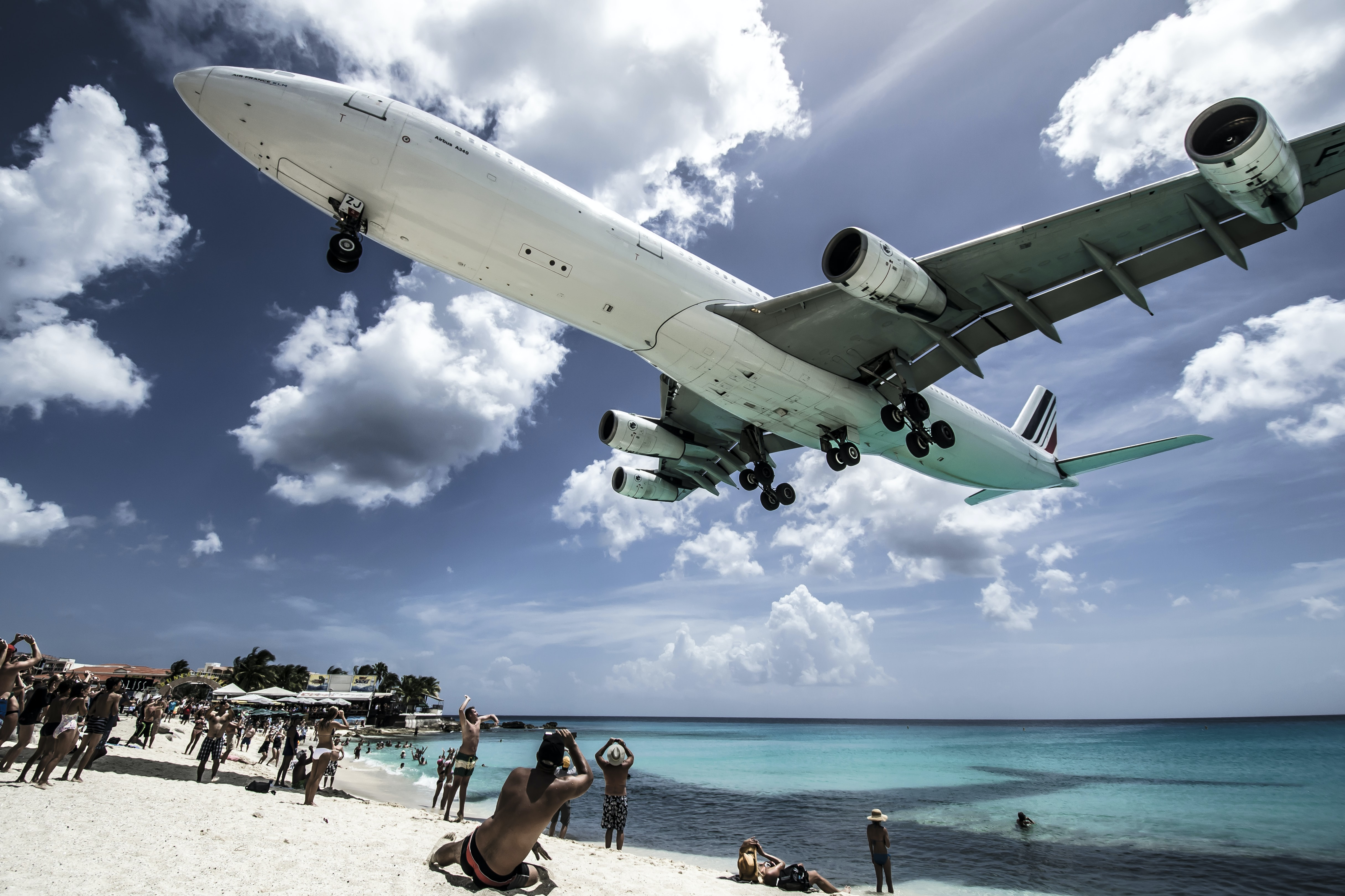 white airplane passing the people at the beach during daytime