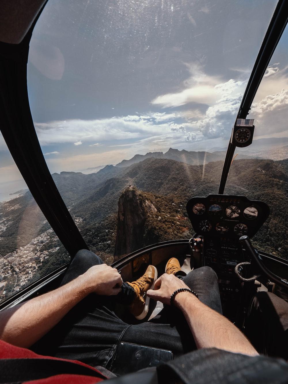 person riding aircraft over the mountain
