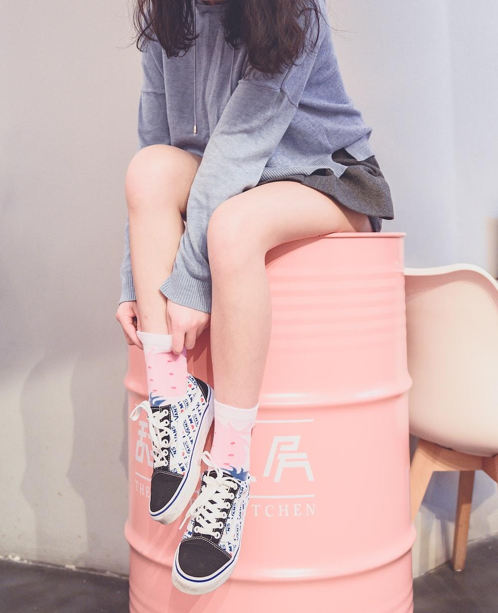 woman sitting on metal barrel