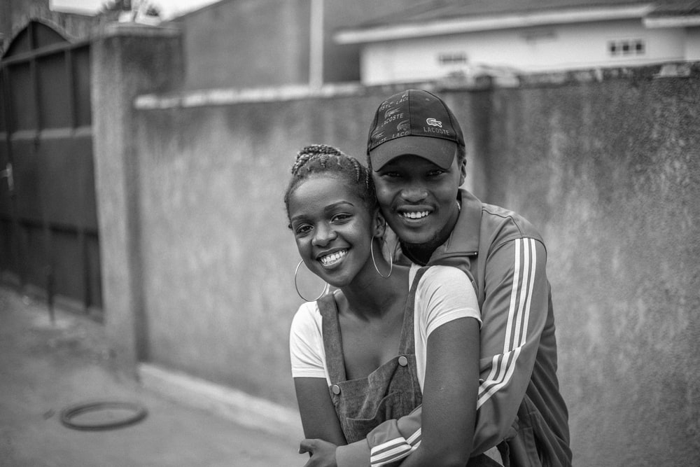 man hugging woman in grayscale photogrpahy