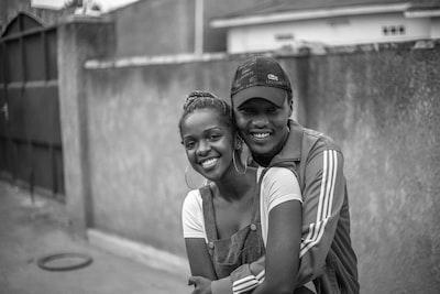 man hugging woman in grayscale photogrpahy rwanda teams background