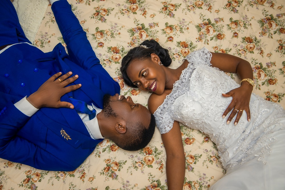man in blue jacket and woman in white wedding gown