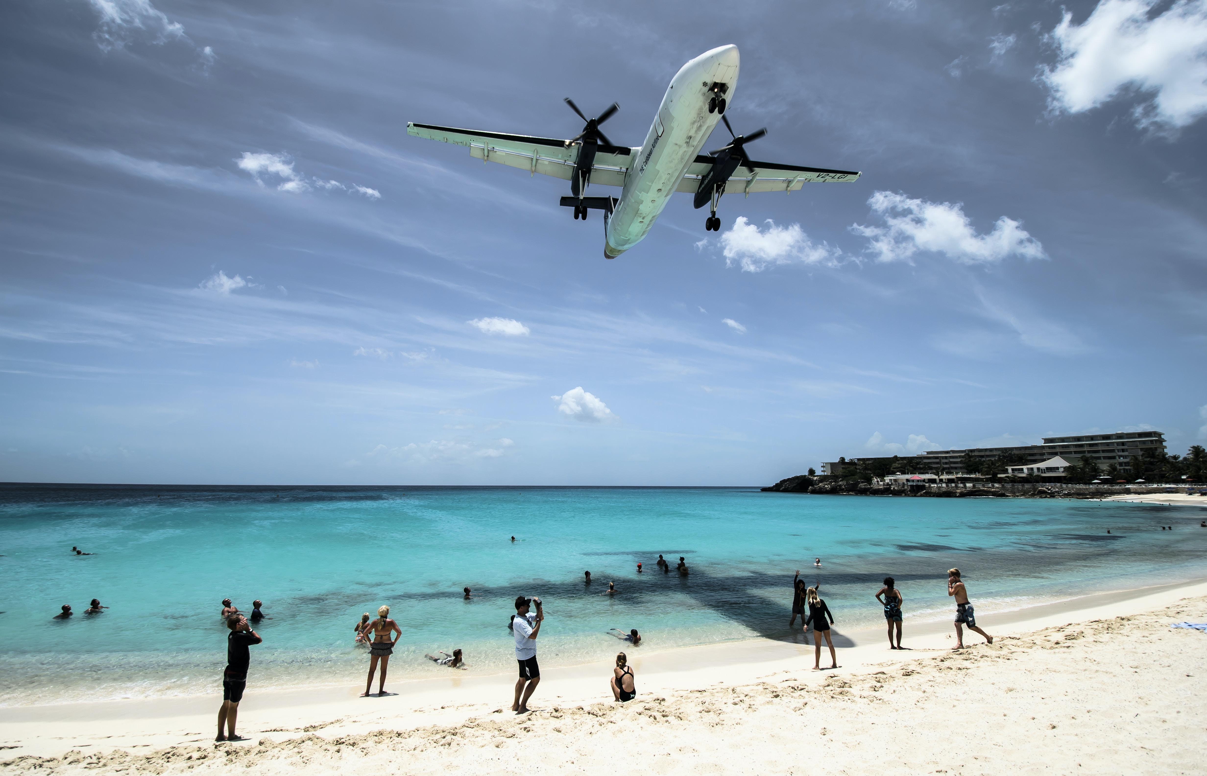 plane flying over seashore during daytime