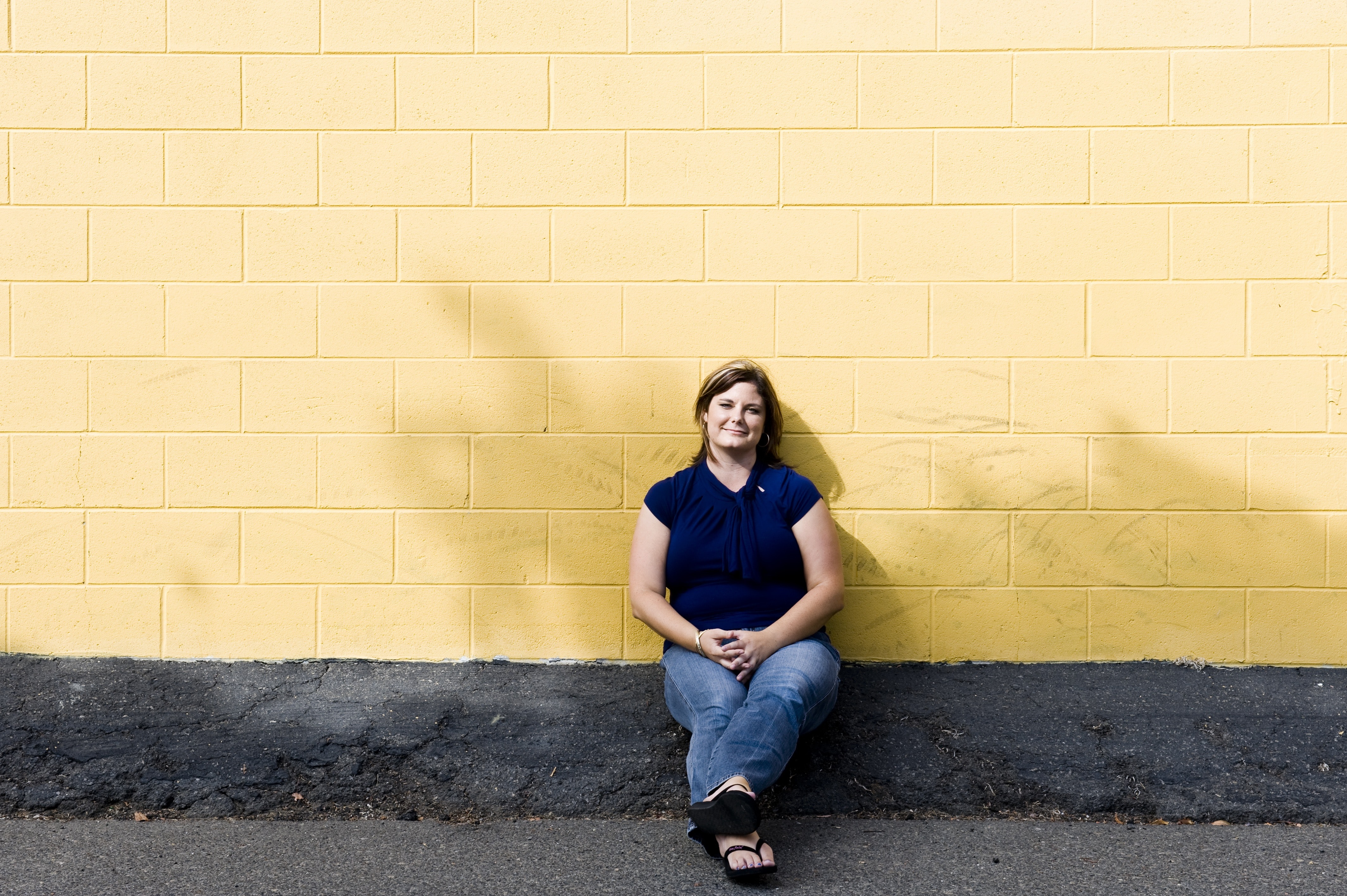 woman in blue shirt leaning on yellow painted wall