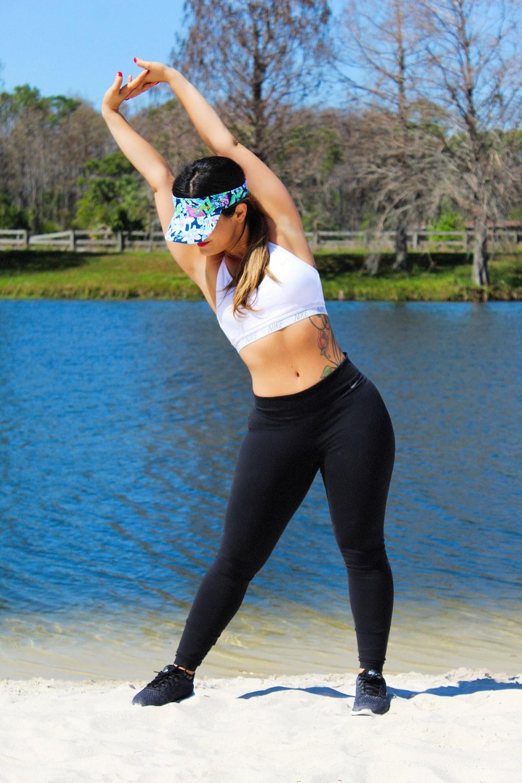 woman wearing white sports bra and black leggings stretching beside lake during day