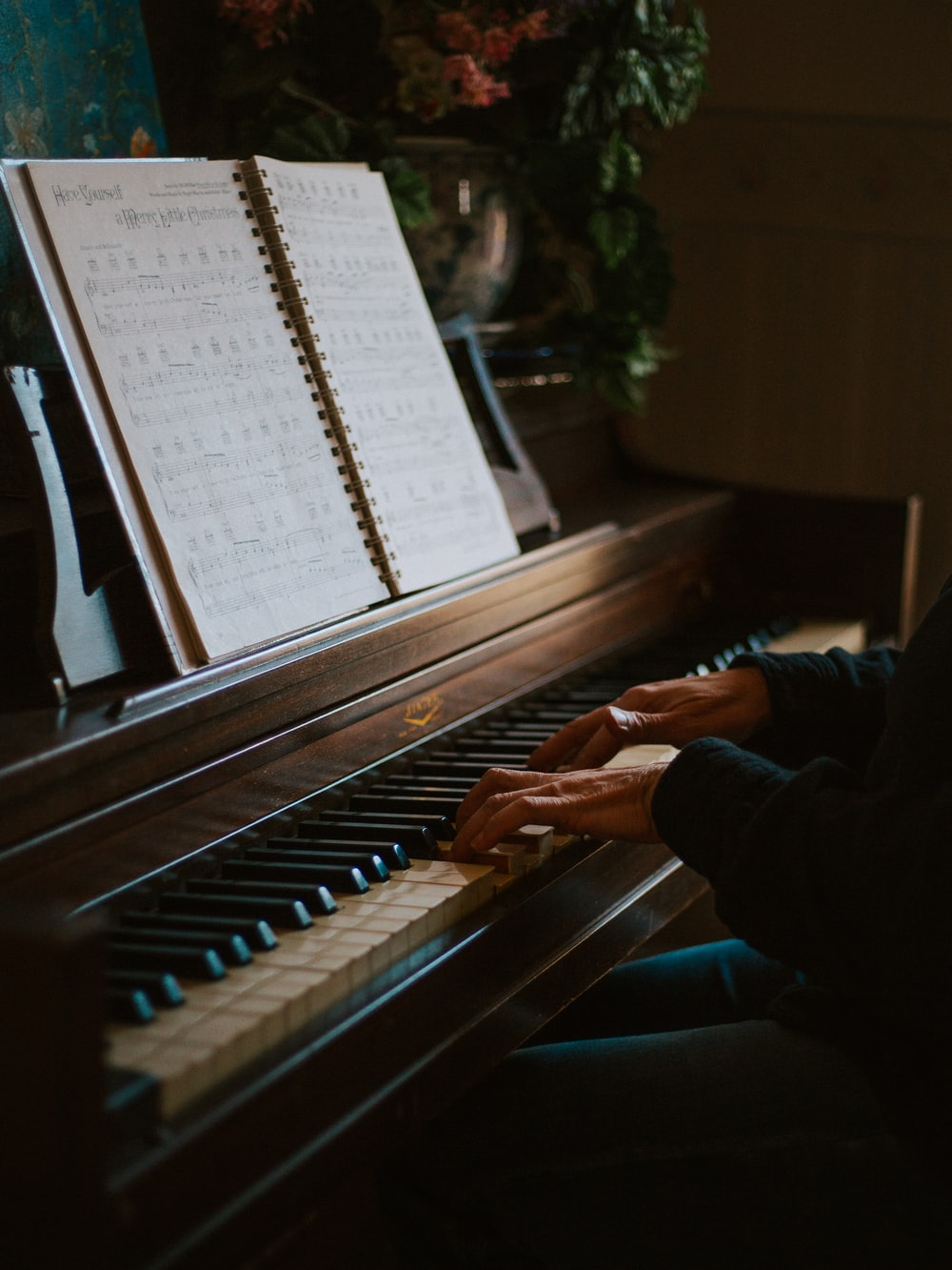 man playing the piano in front of open music book