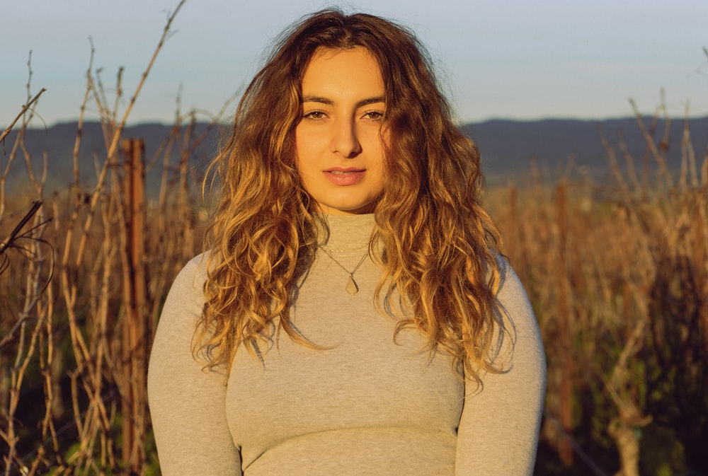 woman wearing grey crew-neck long sleeved shirt surrounded by brown field