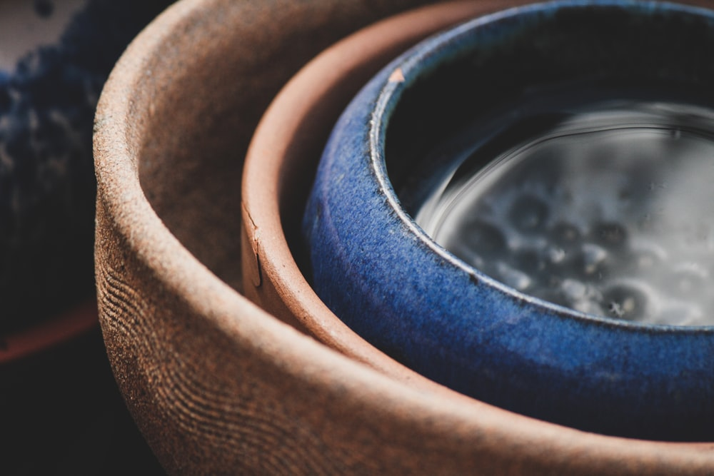 selective focus photography of blue and brown clay pots