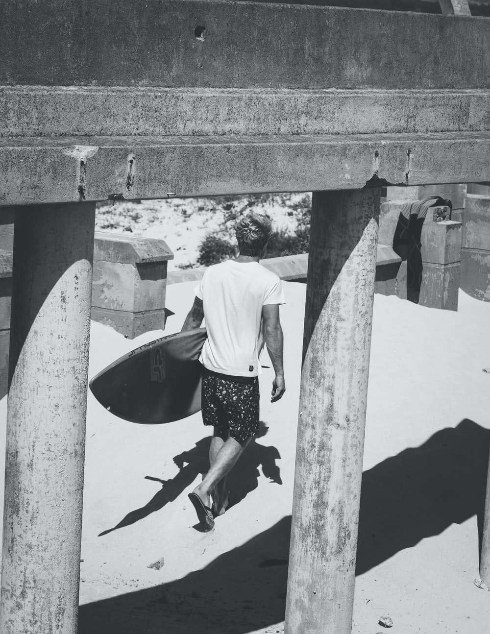 grayscale photography of man holding surf board