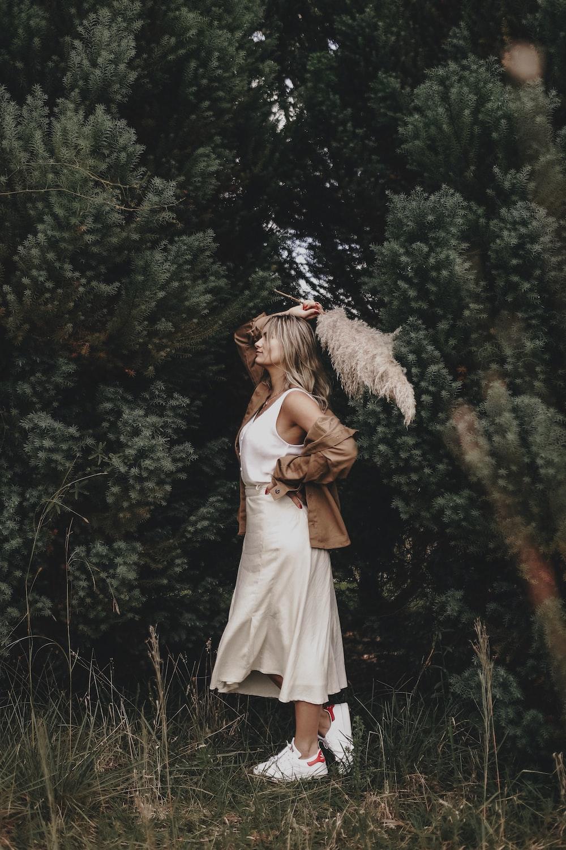 woman wearing white dress standing beside tree