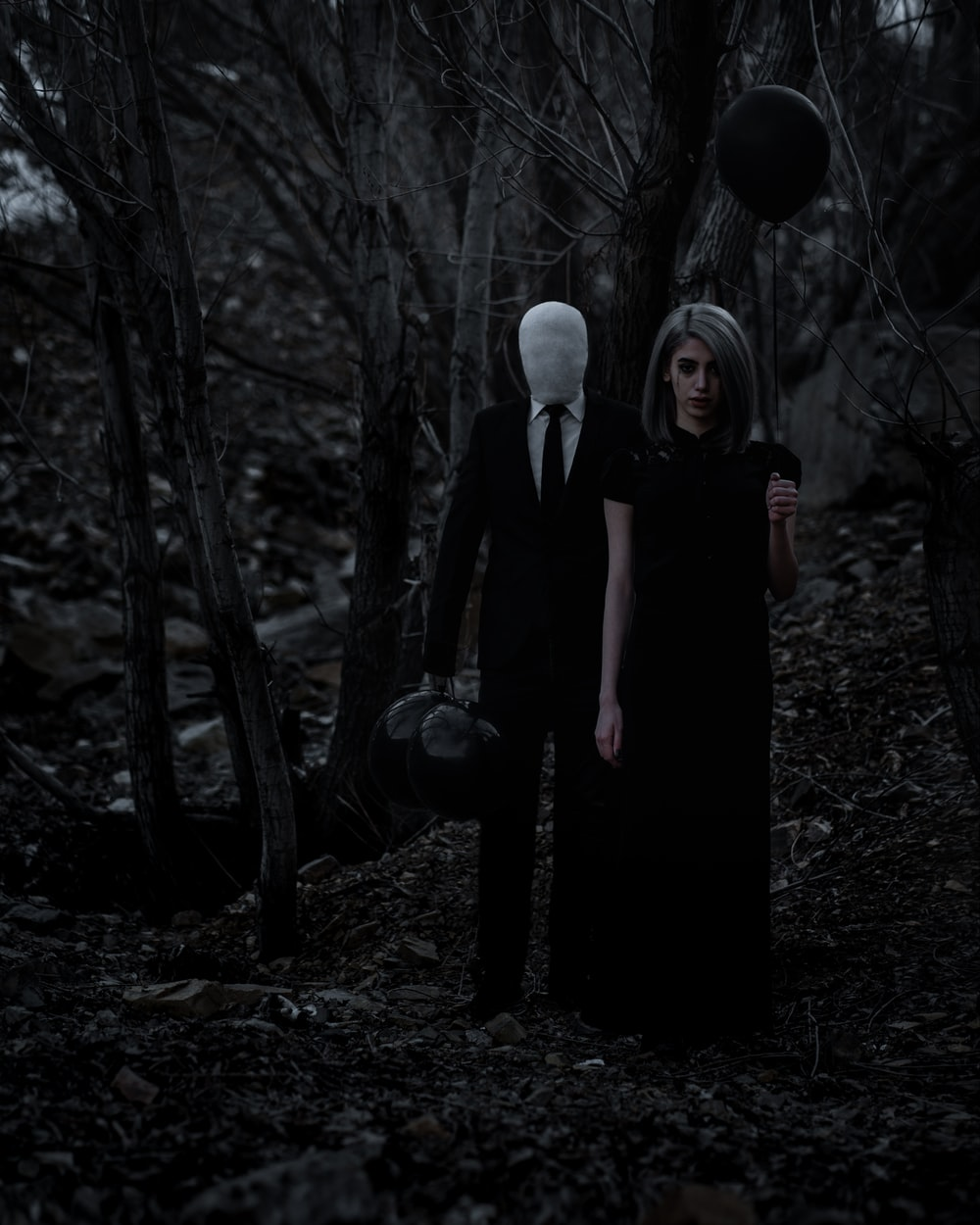 man and woman standing in the middle of forest