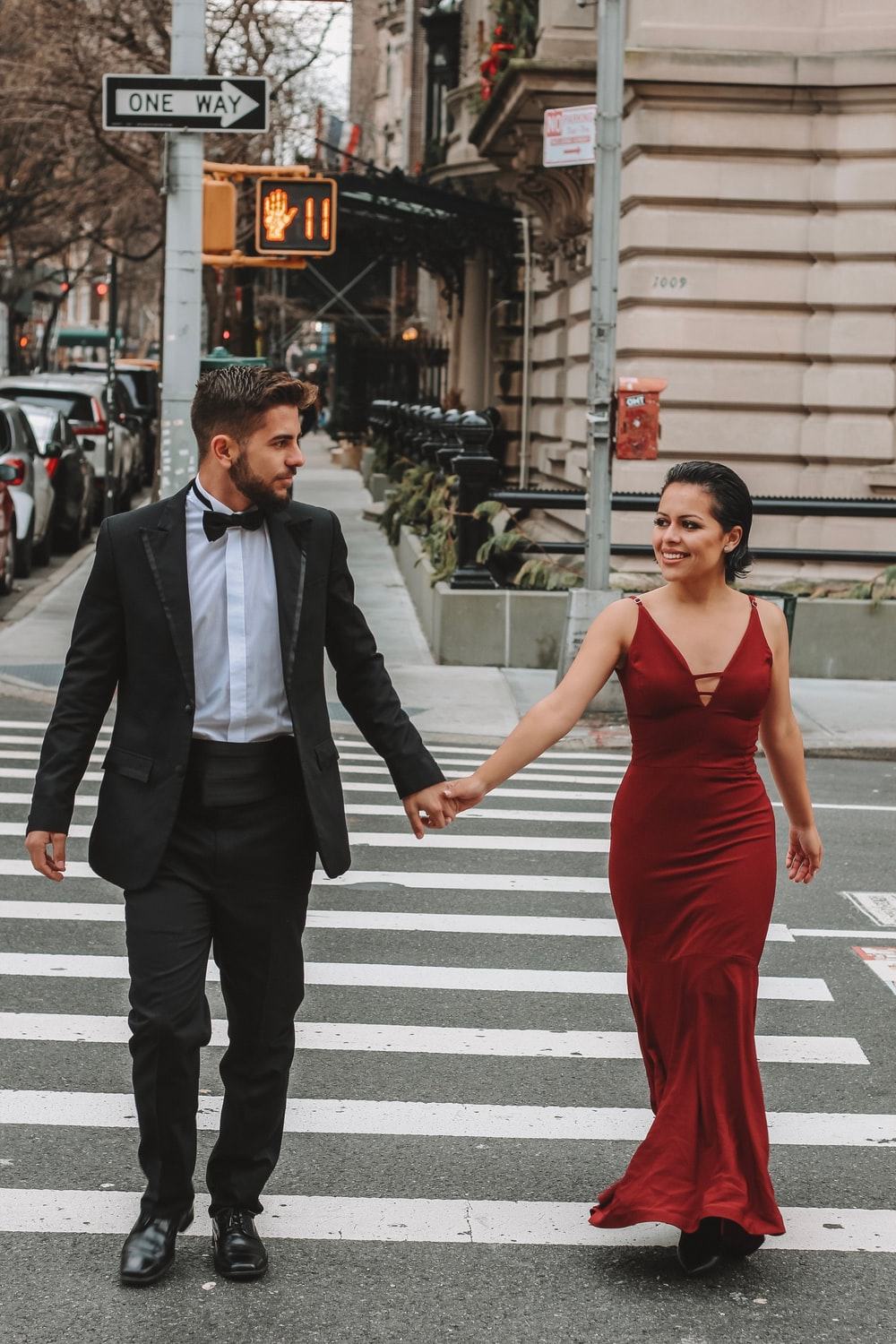 man and woman crossing the street at the pedestrian lane