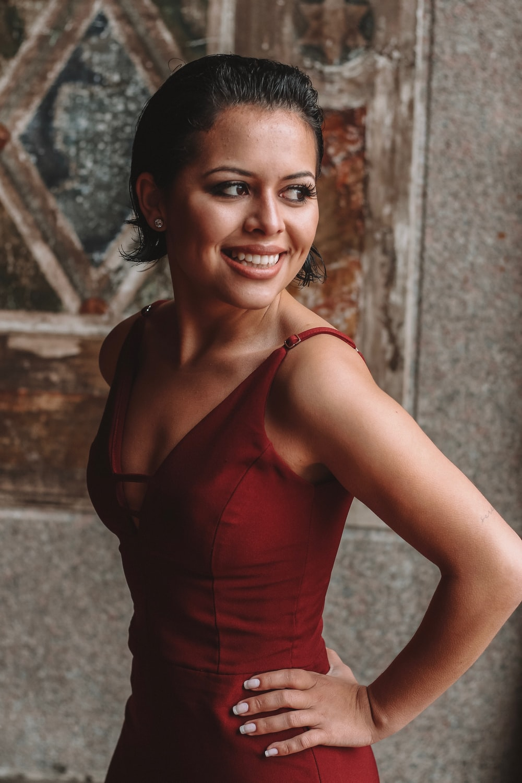 smiling woman wearing red V-neck sleeveless dress