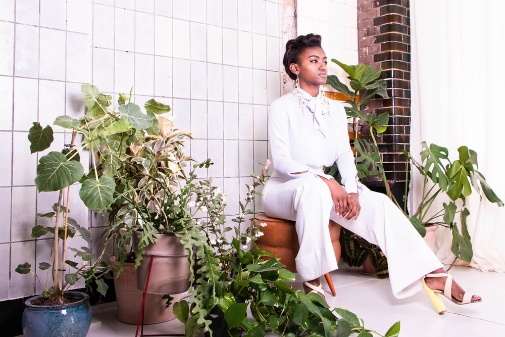 sitting woman wearing withe long-sleeved shirt and pants surrounded by plants