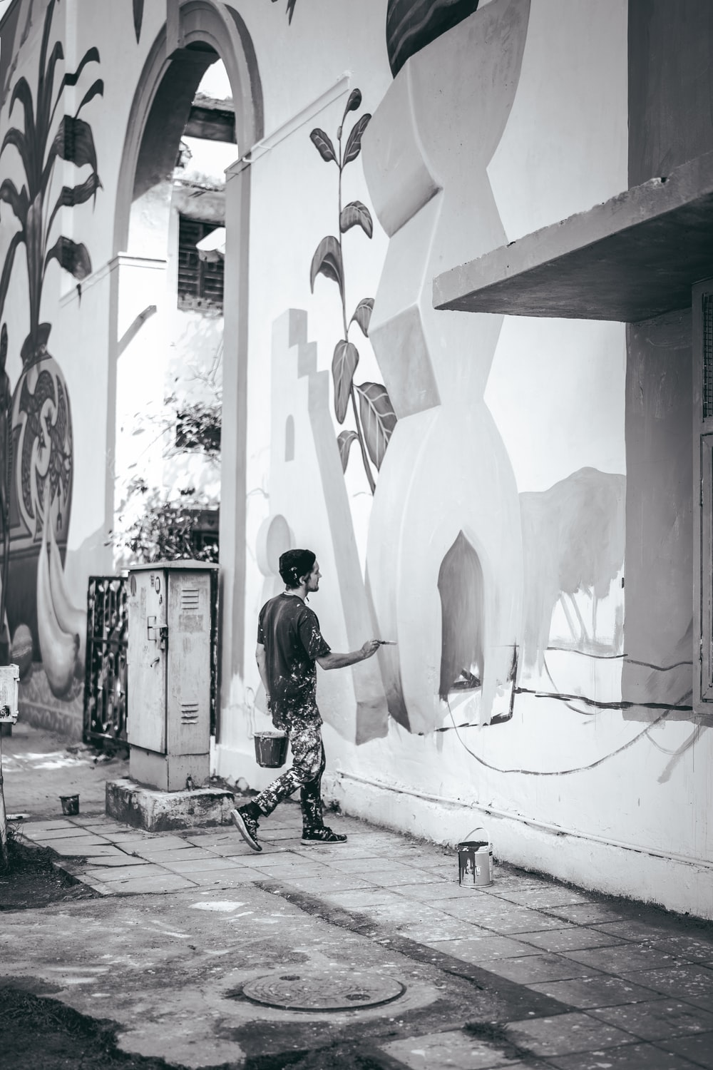 greyscale photo of man painting on wall