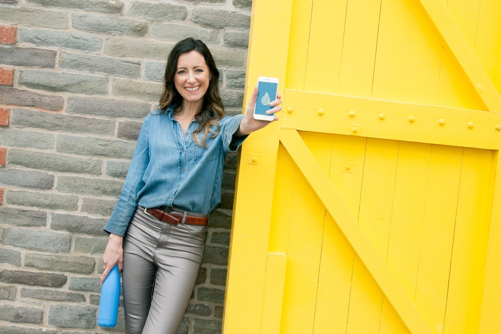 woman wearing blue dress holding smartphone