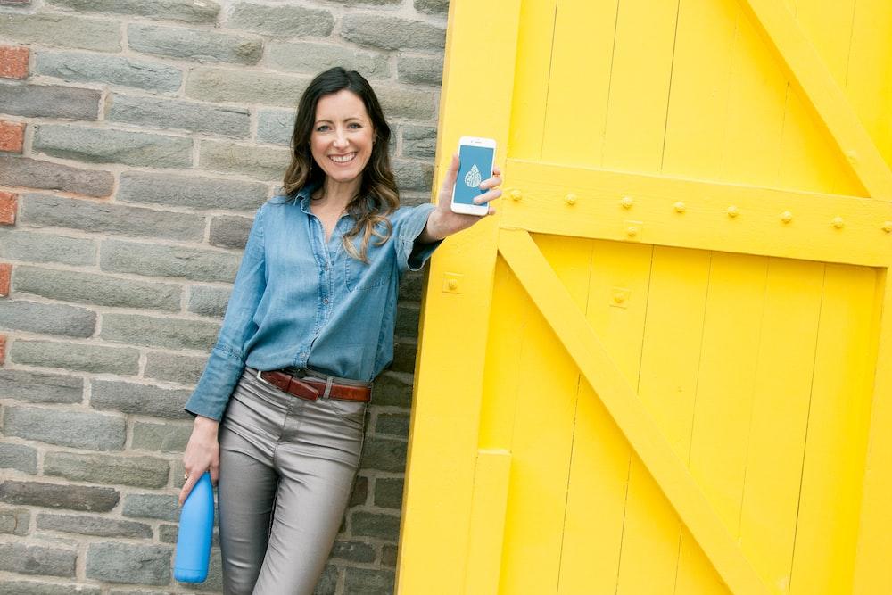 woman wearing blue dress holding smartphone