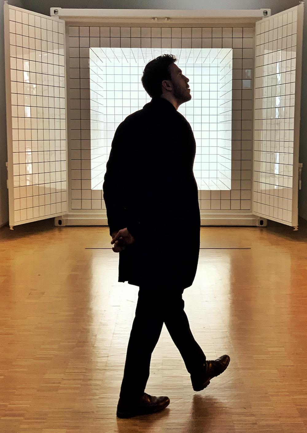 man in black coat standing inside room