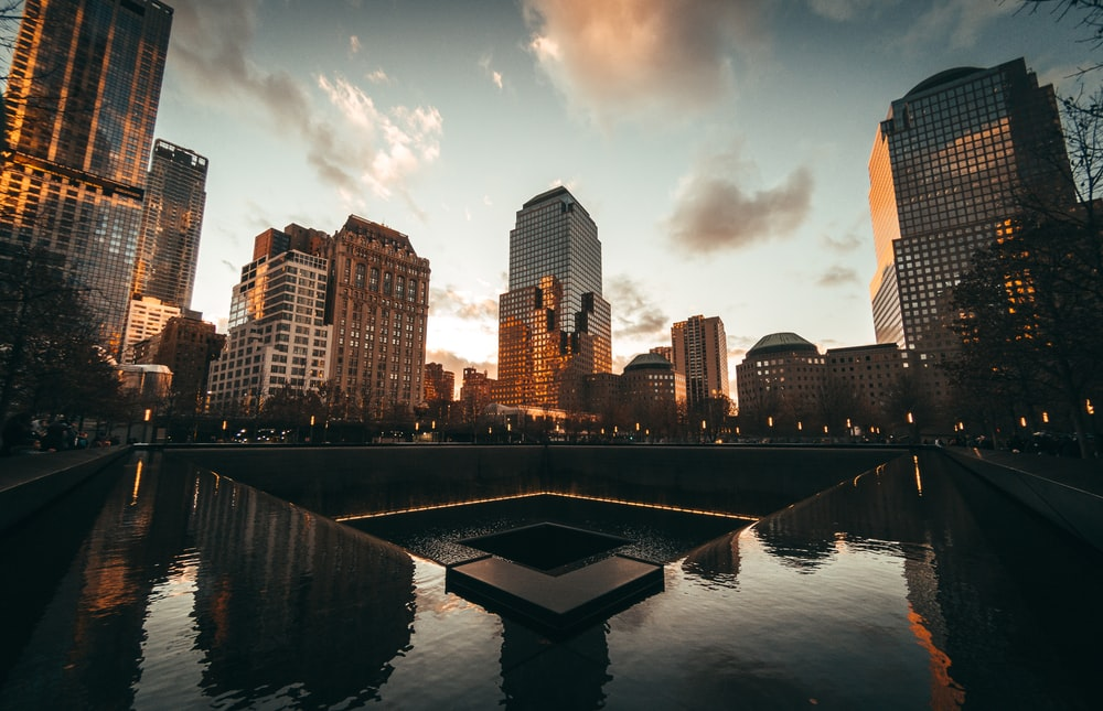 body of water near high rise buildings during golden hour
