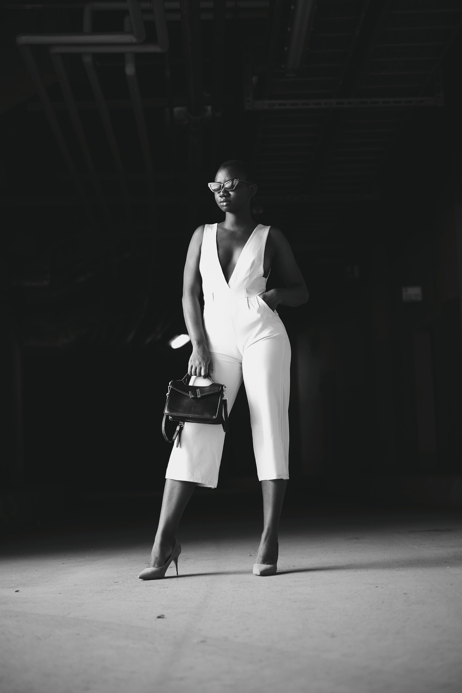 grayscale photography of woman holding handbag