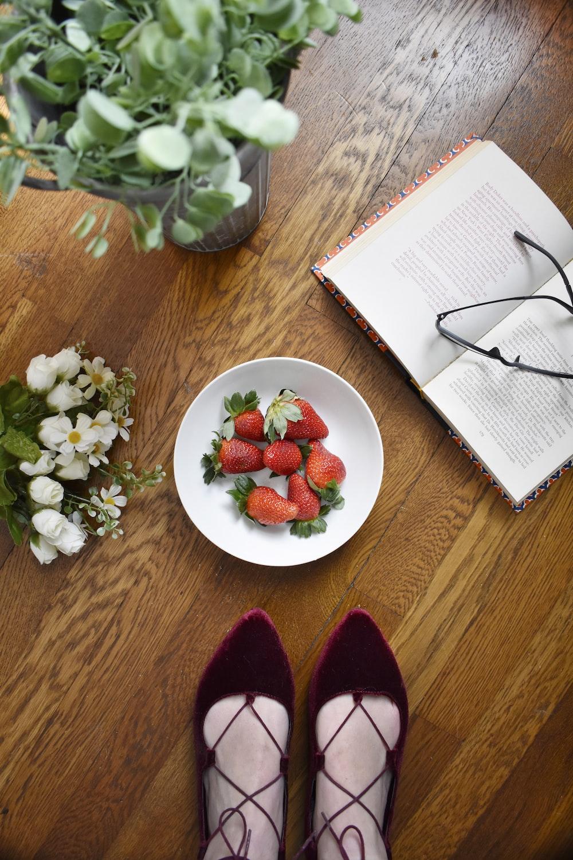strawberries on bowl beside book