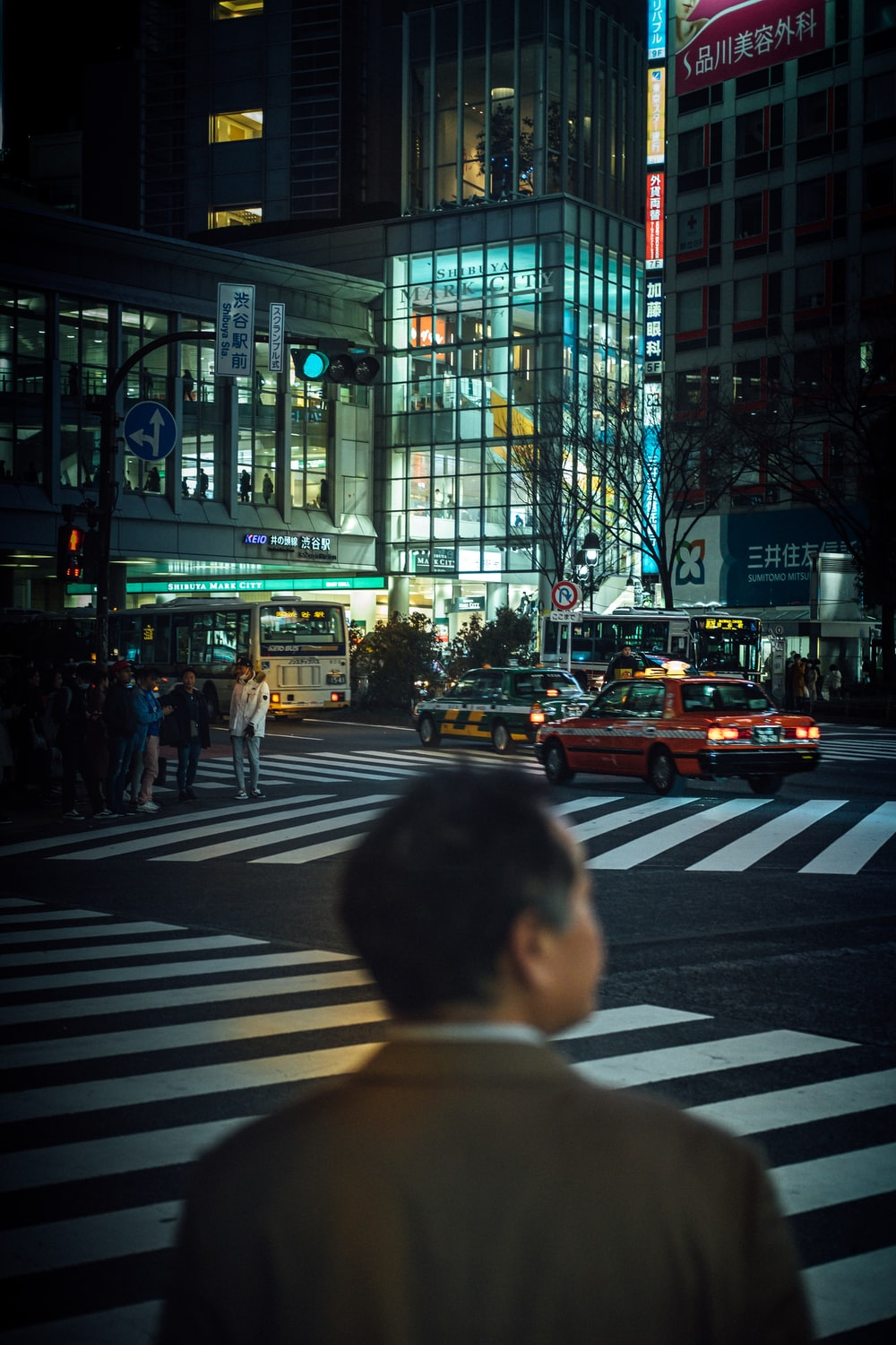 man standing near road beside buildings during night time