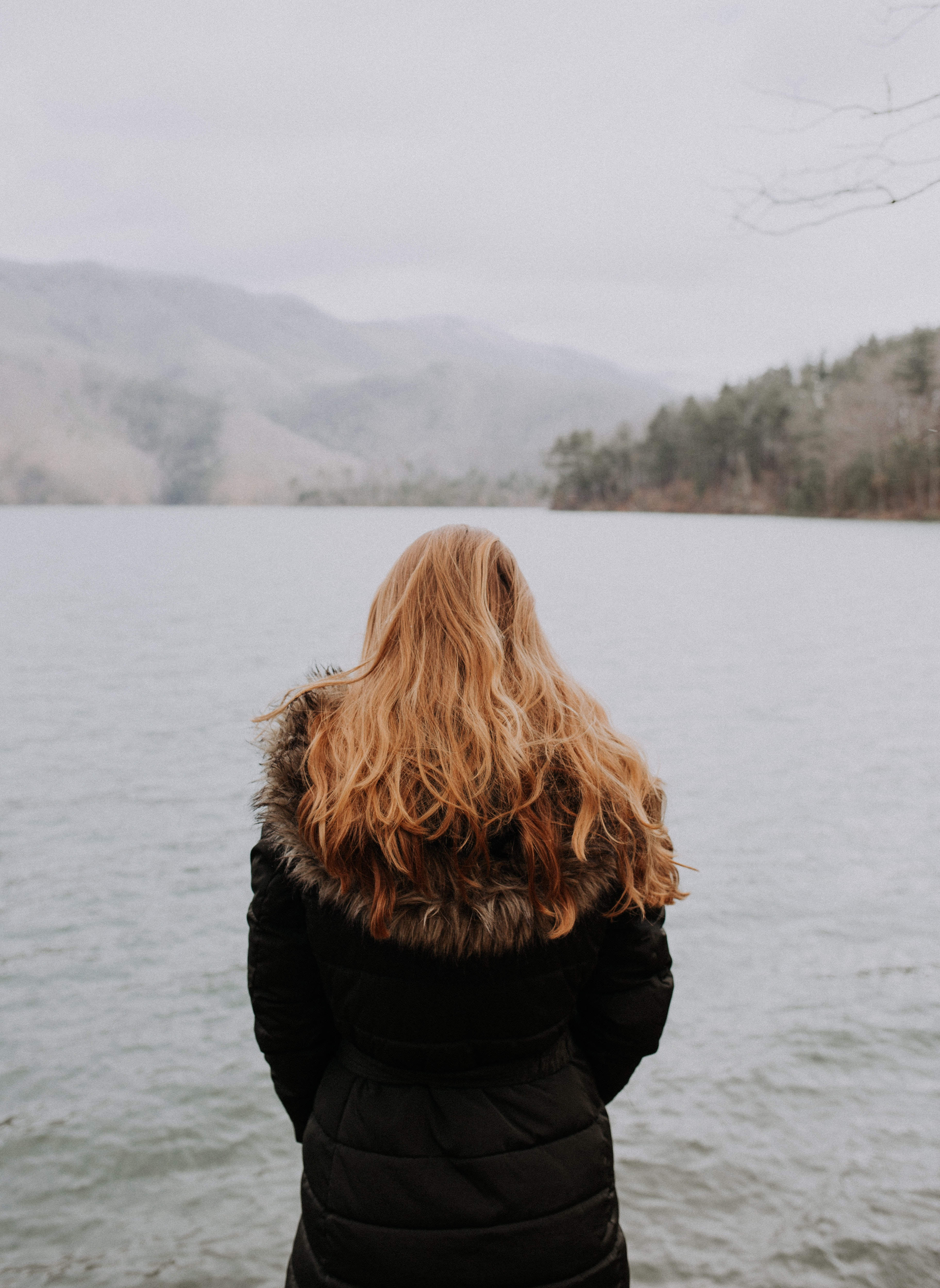 woman standing beside body of water