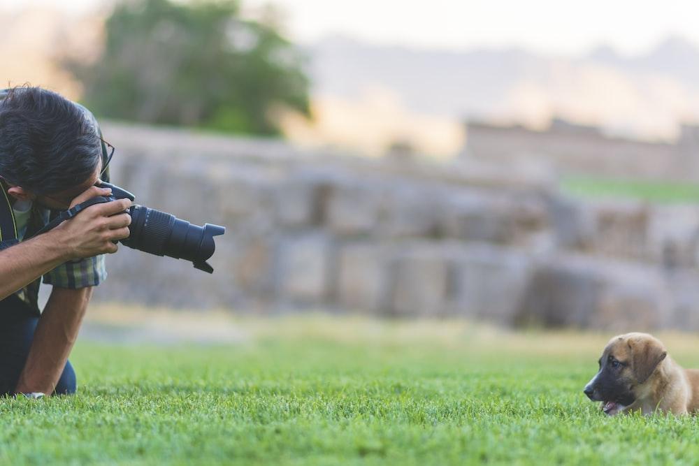 man taking photo of brown puppy using DSLR camera