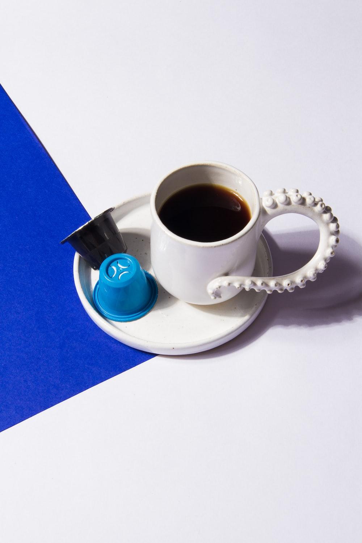 white ceramic mug with coffee on white tray